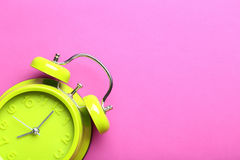 Alarm clock. Green alarm clock on a pink background Royalty Free Stock Photo