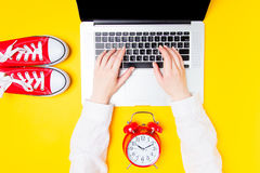 Alarm clock and gumshoes near females hands on laptop Stock Image