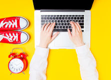 Alarm clock and gumshoes near females hands on laptop Royalty Free Stock Image