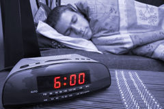 Alarm clock guy. Alarm clock with male model in bed in background. Shallow depth of field Royalty Free Stock Image