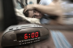 Alarm clock guy. Alarm clock with male model in bed in background. Shallow depth of field, motion blur to show critical realisation Stock Images