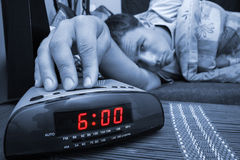 Alarm clock guy. Alarm clock with male model in bed in background. Shallow depth of field Royalty Free Stock Photo