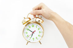 Alarm clock in a hand. On a white background Stock Photo