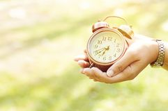 Alarm clock in hand on natural background. Summer Concept royalty free stock photography