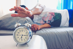 Alarm clock. Hand turns off the alarm clock waking up at morning . soft skin tone effect Royalty Free Stock Images