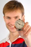Alarm clock in hands. Young nice, smiling guy with an alarm clock in hands, close up Royalty Free Stock Photo