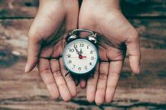 Alarm clock in hands Stock Photo