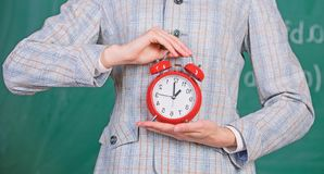 Alarm clock in hands of teacher or educator classroom chalkboard background. School discipline concept. Schedule and. Regime. Alarm clock in female hands close royalty free stock image
