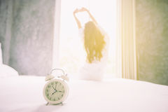 Alarm clock having a good day of Asian woman waking up in her be Stock Photography