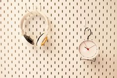 Alarm clock and headphones hung on a white wall .Blank space for text and images.  royalty free stock photos
