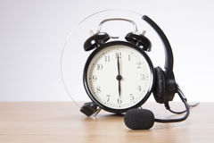 Alarm clock with headset on desk royalty free stock photography