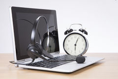 Alarm clock and headset on laptop keyboard Royalty Free Stock Photography