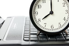 Alarm clock and laptop Stock Images