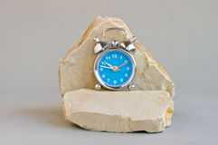 Alarm clock on limestone rock Royalty Free Stock Photo