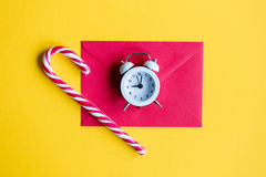 Alarm clock and lolipop with red envelope. Christmas alarm clock and lolipop with red envelope on yellow background Stock Image