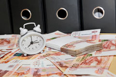 An alarm clock and a lot of Russian money on the Royalty Free Stock Images