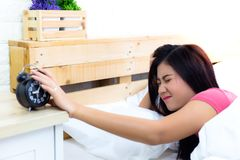 Alarm clock is so loud and wakes beautiful woman up. Attractive royalty free stock image