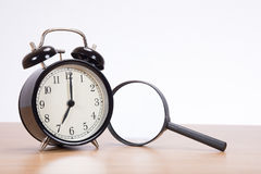 Alarm clock with magnifying glass on desk royalty free stock images