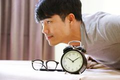 Alarm clock with a man on the bed Stock Photography