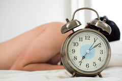 Alarm clock with man waking up on bed in background (Shallow dep Royalty Free Stock Photo