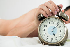 Alarm clock with man waking up on bed in background (Shallow dep Royalty Free Stock Images