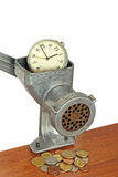 Alarm clock in manual meat grinder and coins on table. Royalty Free Stock Photo