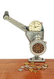 Alarm clock in manual meat grinder and coins on wooden table. Royalty Free Stock Photography
