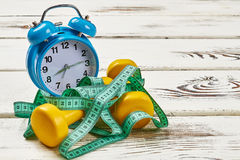 Alarm clock and measuring tape. Stock Image