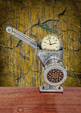 Alarm clock in meat grinder on grunge scratched background. Royalty Free Stock Images