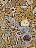 Alarm clock in meat grinder on old metal keys background. Stock Image