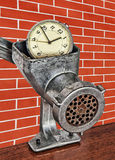Alarm clock in meat grinder on red brick wall background. Stock Photo