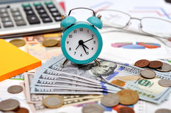 Alarm clock. Money and calculator on the table Royalty Free Stock Photos