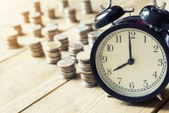 Alarm clock and money coin on wood table. Saving money concept Royalty Free Stock Photo