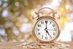 Alarm clock and money coins stack Stock Photo