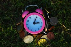 Alarm clock and money, coins stack and alarm clock on grass, finance concept, business background and selective focus. Cash, time is money royalty free stock image