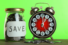 Alarm clock and money in a glass jar Royalty Free Stock Image
