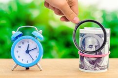 Alarm clock and money on green bokeh background. The concept of Time is money. Business financial ideas. Saving. Financial royalty free stock image