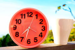 Alarm clock on natural landscape season park with coffee cup Stock Images