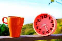 Alarm clock on natural landscape season park with coffee cup Royalty Free Stock Photo