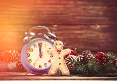 Alarm clock near Pine branches and gingerbread on wooden table. Royalty Free Stock Image