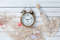 Alarm clock and net with shells and bottle Stock Photo