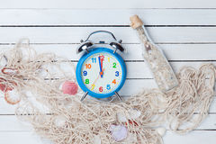 Alarm clock and net with shells and bottle Stock Images
