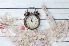 Alarm clock and net with shells and bottle Stock Image
