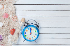 Alarm clock and net with shells and bottle Royalty Free Stock Images
