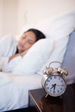 Alarm clock next to bed in which woman is sleeping Stock Image
