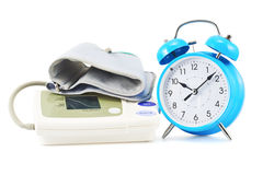 Alarm clock next to sphygmomanometer Stock Photos