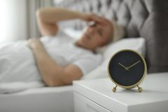 Alarm clock on nightstand with mature woman royalty free stock image