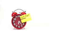 Alarm clock with a note don't forget. Retro alarm clock with sticky note pad Stock Image