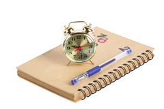 Alarm clock and notebook Stock Images