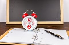 Alarm clock with notebook and black pen on wooden board Royalty Free Stock Images